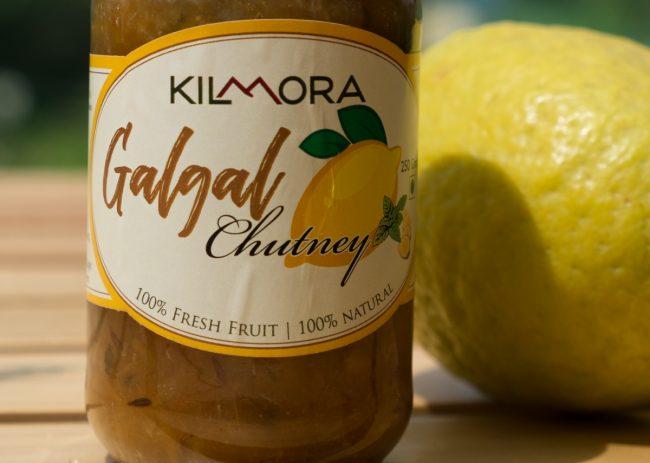 Galgal (Hill Lemon) Chutney bottle displayed against the sky with a hill lemon