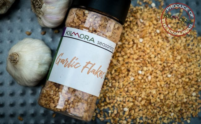 Raw garlic bulbs on the left of frame with a jar of Garlic Flakes in the middle and garlic flakes sprinkled next to the jar
